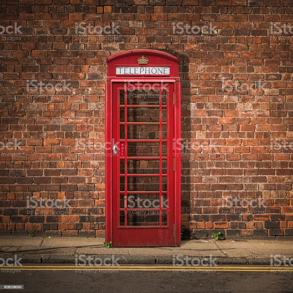 British Phone Box Against Red Brick Wall stock photo