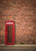 Traditional Red British Telephone Box Against A Red Brick Wall With Copy Space