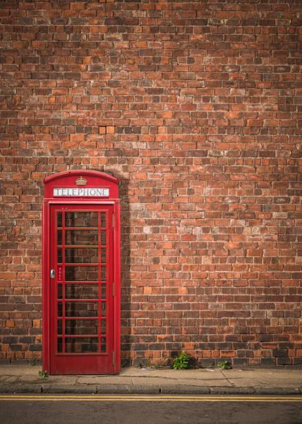 british phonebox against red brick wall - phone, travelling, copy space imagens e fotografias de stock