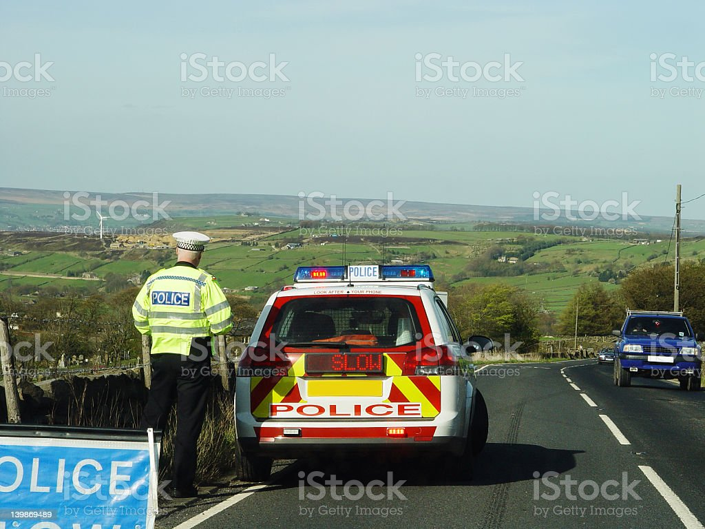 British police car with slow sign on the side of the road stock photo