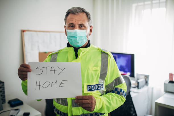 British police officer holding paper with message stay home stock photo