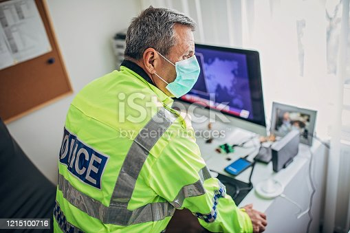 Senior British police officer with protective mask in the office. Fight against coronavirus.