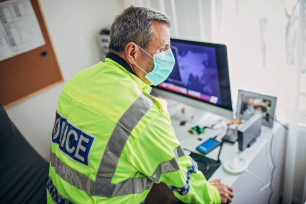 British police officer in the office Senior British police officer with protective mask in the office. Fight against coronavirus. civil servant stock pictures, royalty-free photos & images