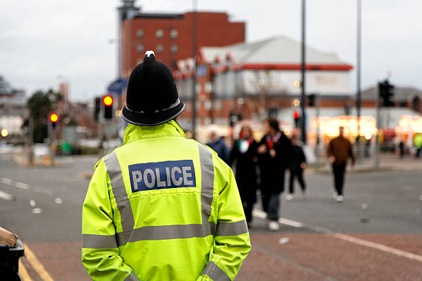 British Policeman Wearing Tradtional  Helmet Observes People-See below for more  northwest england stock pictures, royalty-free photos & images