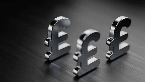 british pound symbols on black wood surface - money black background stock photos and pictures