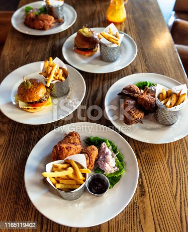 Plates of food in an English pub with burgers, fried chicken and fries.