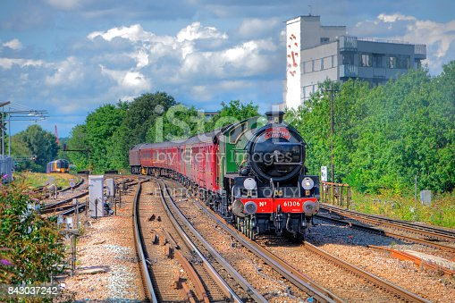 "Clapham Junction, United Kingdom – Aug 29, 2015:  British Railways steam locomotive #61306 ""Mayflower"" (2-6-0) arrives at Clapham Junction with ""The Cathedral Express"" tour train."