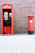 Single red british telephone box with a red post box with no people