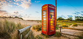 Red telephone box set amongst the golden sand dunes of a summer seaside beach illuminated by the warm sunlight of daybreak. ProPhoto RGB color profile for maximum color gamut.