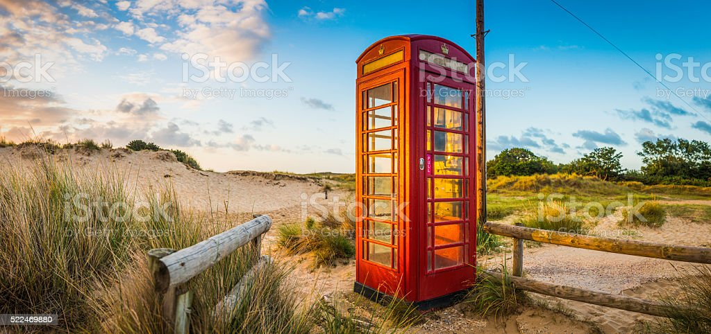 British red telephone box illuminated at sunrise on seaside beach stock photo