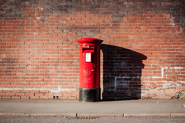 British Royal Mail Postbox Glasgow, UK - April 6, 2014: A bright red Royal Mail British postbox on the street. theasis stock pictures, royalty-free photos & images