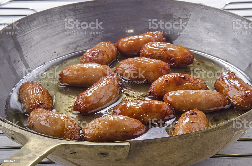 british sausages in a brass pan stock photo