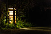 British telephone box at night in remote Welsh country lane