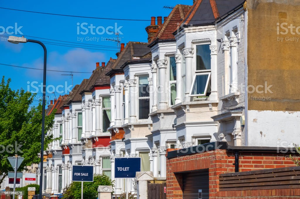 British terraced houses in London with estate agent boards royalty-free stock photo