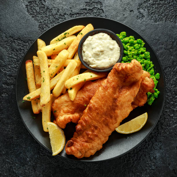 British Traditional Fish and chips with mashed peas, tartar sauce and cold beer. stock photo