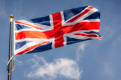 A large UK flag flying in the wind.