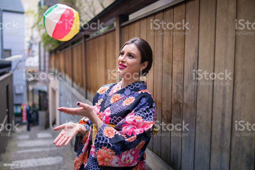 British woman in kimono having fun with paper balloon, traditional Japanese toy stock photo