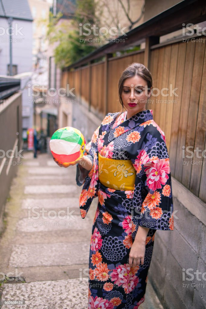 British woman in kmono holding, paper balloon, traditional Japanese toy stock photo