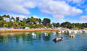 Tourists at the shore of Saint Guirec at the pink granite coast in Brittany, Franceduring a beautiful summer day.
