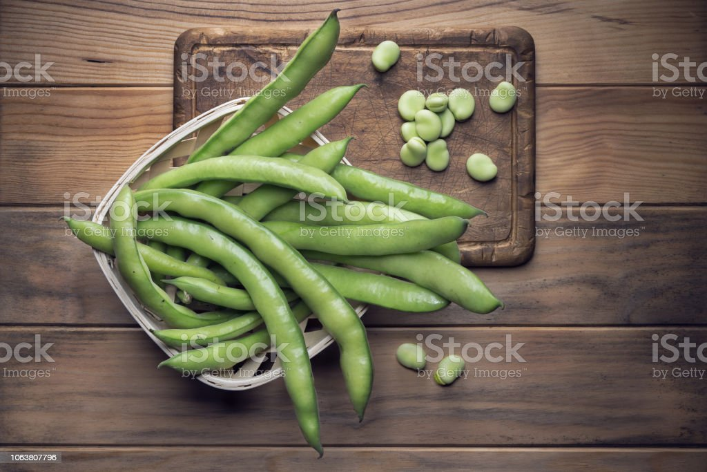 Broad bean pods and seeds on wooden background stock photo