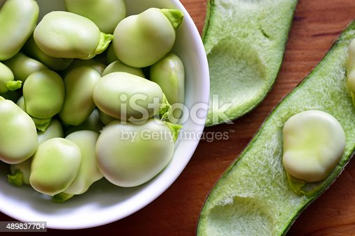 Broad beans fava beans in bowl on wooden table. Summer vegetables, legumes. Top view.