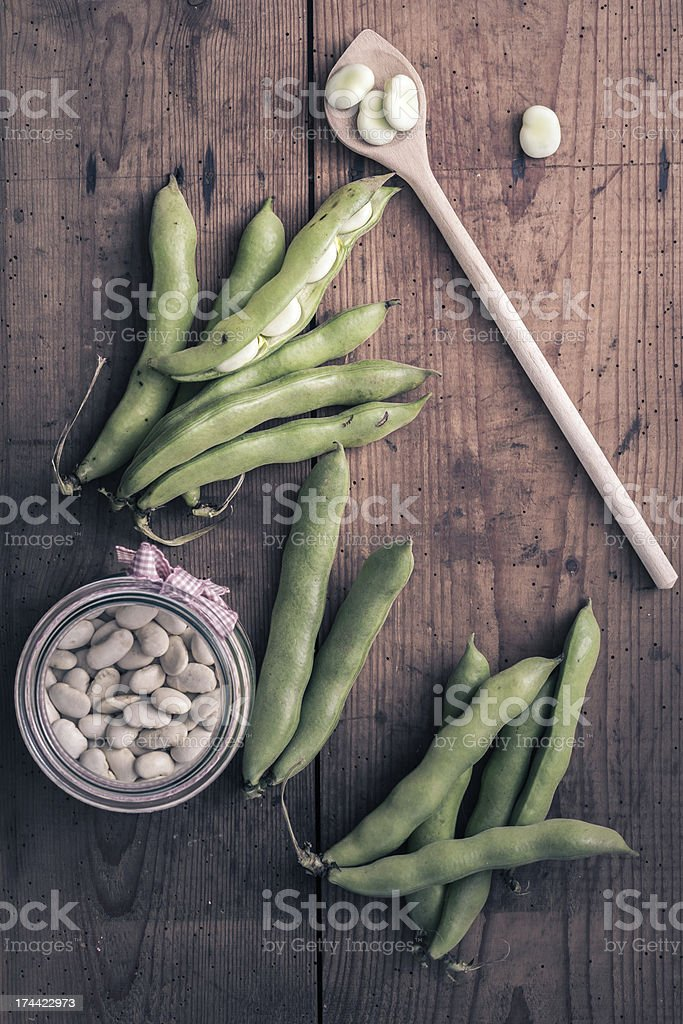 Broad Beans on a wooden Table with Jar stock photo