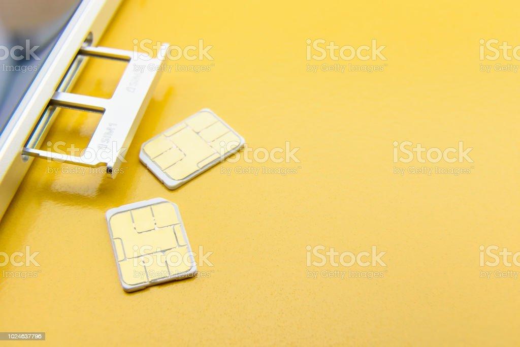 Concepto de tecnología de comunicación móvil de 5G banda ancha: bandeja de tarjeta SIM / ranura para tarjeta SIM dual con dos nano SIM tarjetas sobre fondo amarillo. SIM almacena la identidad internacional de suscriptor móvil número IMSI. - Foto de stock de 5G libre de derechos