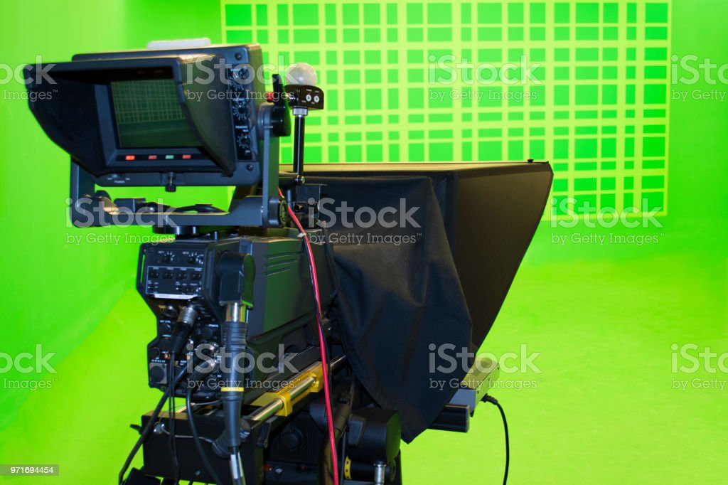 Broadcast television studio camera in green screen studio room with LED lights on the ceiling. stock photo