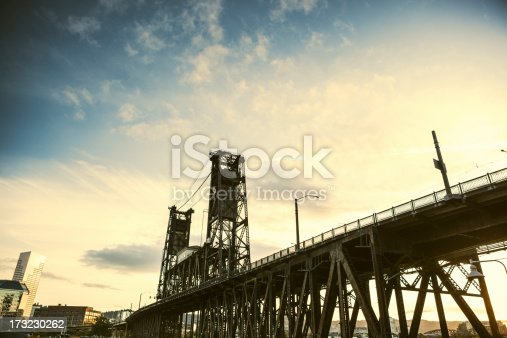 A sunset wide angle view of the steel bridge crossing the Willamette river in Portland, Oregon.  The city is visible in lower image left.  Horizontal with copy space in the blue and orange sky.