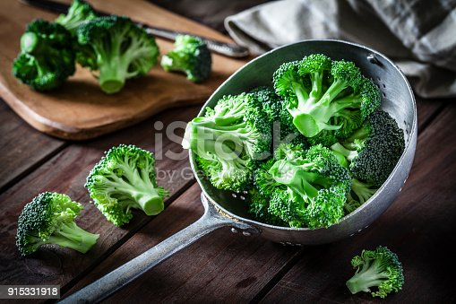 Fresh organic broccoli in an old metal colander shot on rustic wooden table. This vegetable is considered a healthy salad ingredient. Predominant colors are green and brown. Low key DSRL studio photo taken with Canon EOS 5D Mk II and Canon EF 100mm f/2.8L Macro IS USM