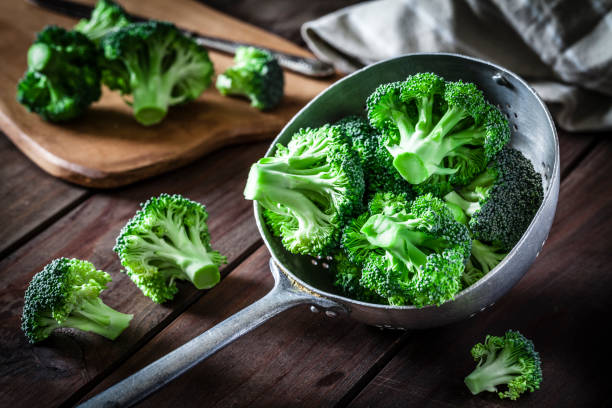 Broccoli in an old metal colander stock photo