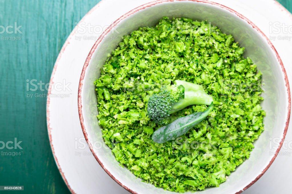 Arroz de brócoli en un recipiente sobre fondo verde. Vista superior. Arriba. Copia espacio. Brócoli desmenuzado. - foto de stock