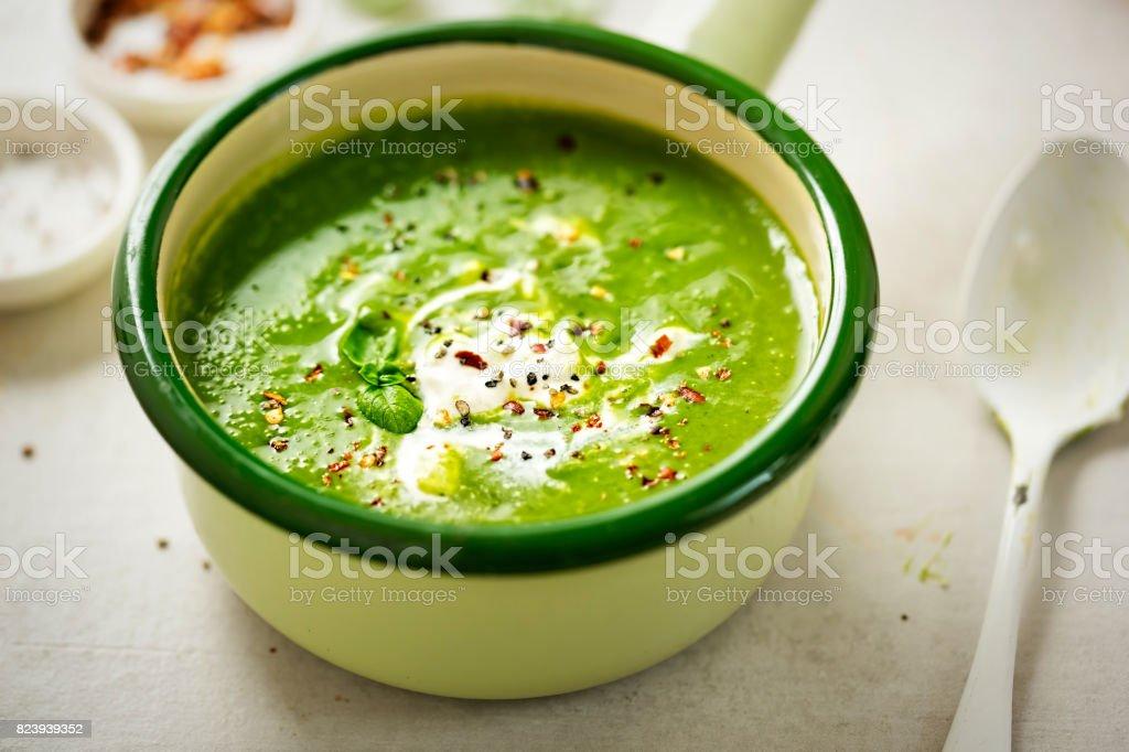 Broccoli spinach pea cream soup with cream and chilli flakes stock photo