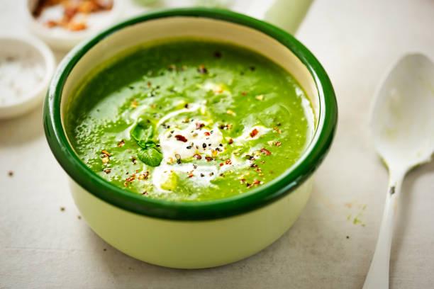 brokkoli spinat creme erbsensuppe mit sahne und chili-flocken - spinatsuppe stock-fotos und bilder