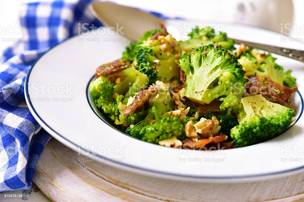 Broccoli with fried bacon and walnuts. stock photo