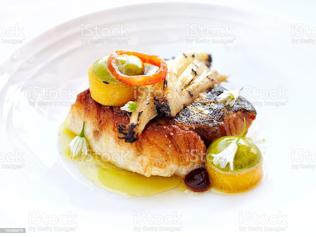 Broiled Alaskan halibut with leeks drizzled in olive oil stock photo