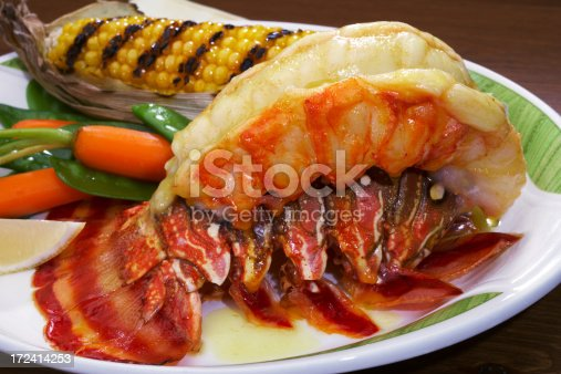broiled Lobster tail elegantly plated prepared with butter and vegetables.