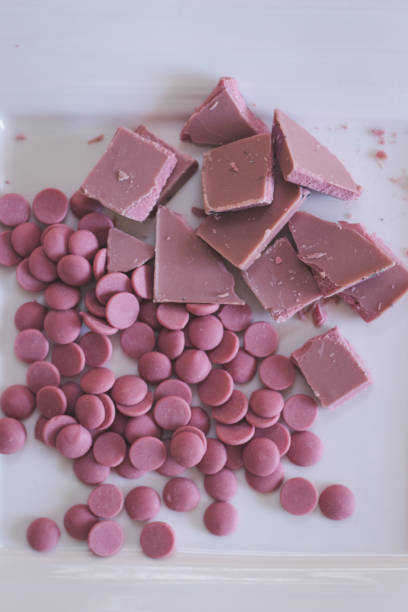 Broken and shattered pieces of ruby red chocolate in a round charcoal stone ceramic bowl. stock photo