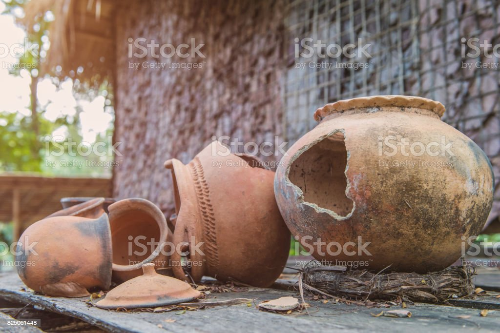 Broken antique clay pot or traditional Jar on abandoned hut stock photo