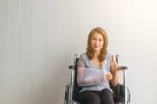 Broken arm Asian woman with arm sling sponsored in her hands sitting on a wheelchair Ideas for accident Injuries and health care Studio shot on a white background. stock photo