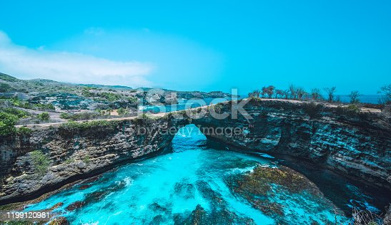 Broken Beach in Nusa Penida, Bali, Indonesia. The sky is blue sky and the ocean is turquoise. In the middle a natural arch.