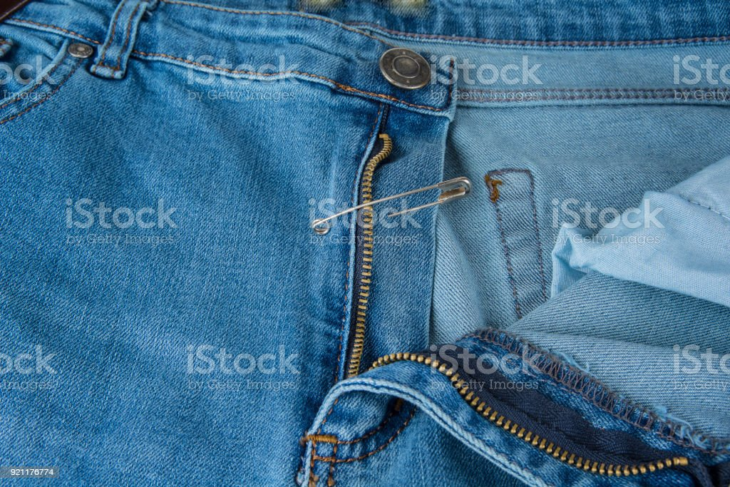 Broken blue jeans zipper fixed with safety pin stock photo