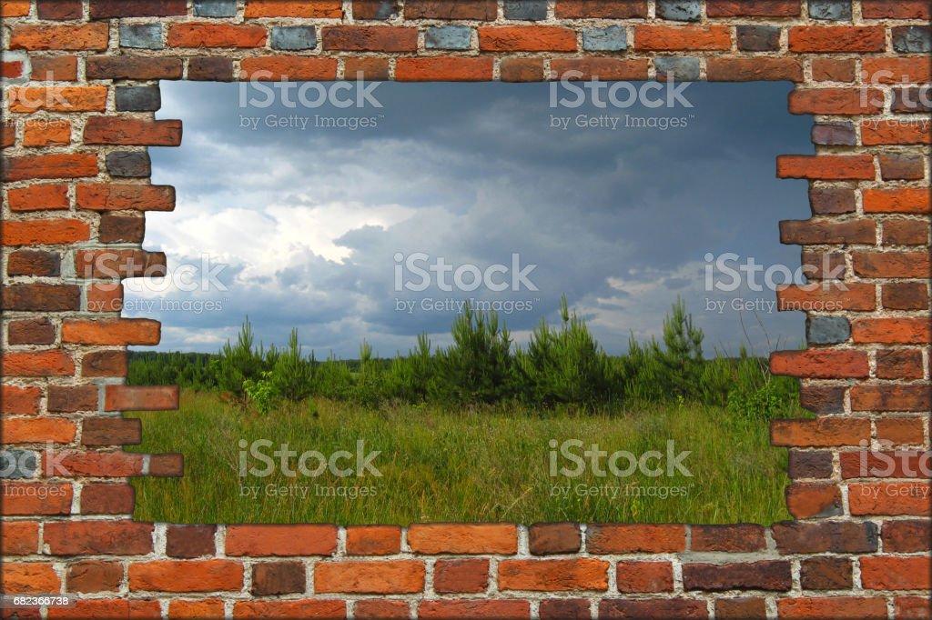 broken brick wall and view to field with dark thunder storm clouds zbiór zdjęć royalty-free