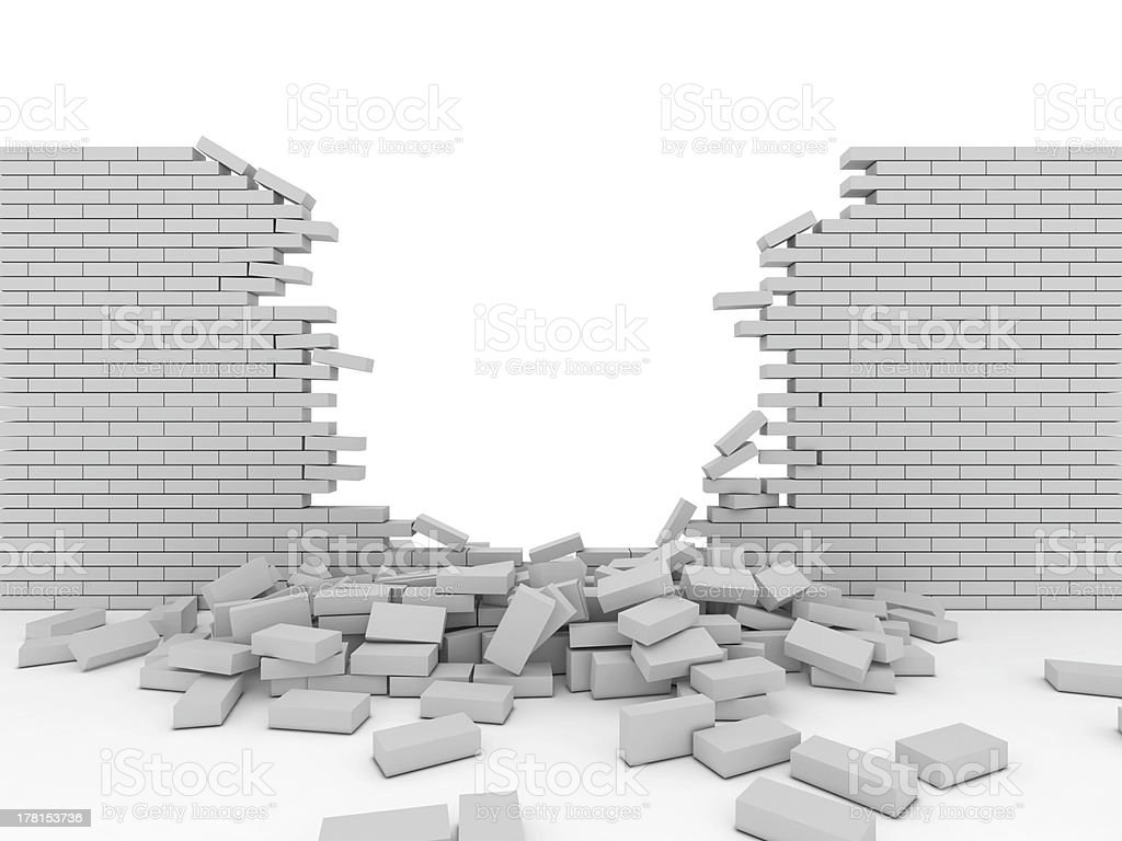 Broken brick wall with bricks lying on the ground stock photo