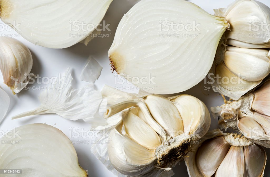 Broken bulbs of garlic and white onions stock photo