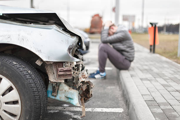 broken car after the accident in  foreground - car accident stock photos and pictures