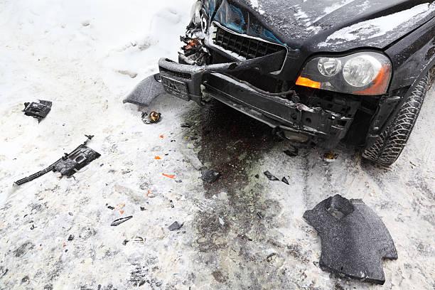 Broken car on road in winter; crash accident stock photo