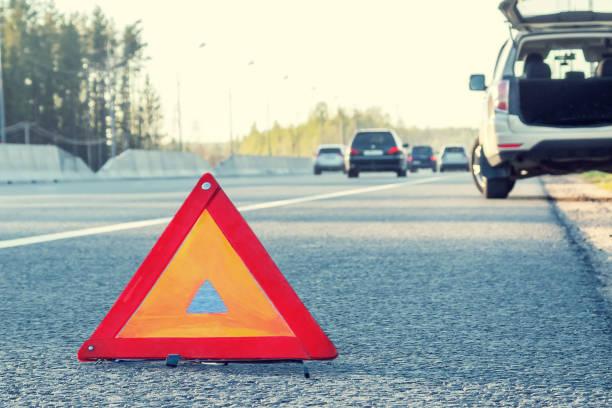 Kaputtes Auto auf der Seite der Autobahn und ein Notstopp-Schild – Foto