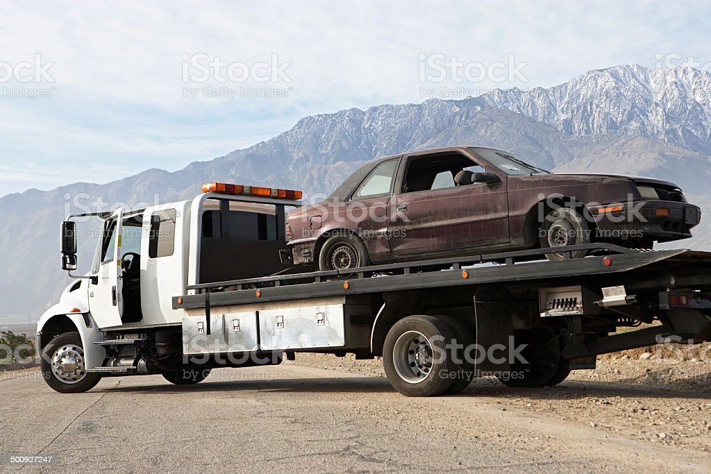 Broken car on tow truck stock photo