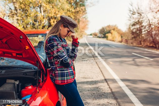 Broken car. Sad woman standing on autumn road by her auto with hood open waiting for help.